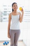 Усмехаясь sporty молодая женщина держа апельсин стоковая фотография
