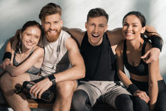 Усмехаясь sporty люди и женщины сидя на стенде в спортзале Стоковая Фотография RF