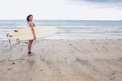 Усмехаясь surfboard нося женщины на пляже Стоковые Изображения