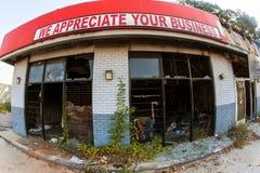 Усмешливый знак сидит над ожогом вне и бесчинствованным мелким бизнесом Стоковые Фотографии RF