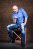 Усмешливый человек сидя около кирпичной стены Стоковое фото RF