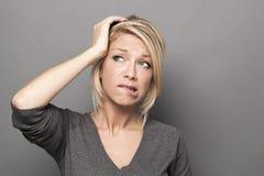 Усомнитесь и потревожьтесь концепция для тревоженой белокурой женщины 20s Стоковое фото RF