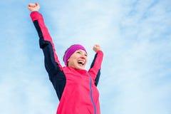 Успех бежать и спорта Счастливая женщина празднуя победу и повышения его руки вверх Женский бегун успешный против голубого неба стоковое фото