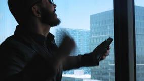 Успех в бизнесе и достижение - праздновать счастливого бизнесмена веселя на сотовом телефоне Молодой городской профессионал видеоматериал