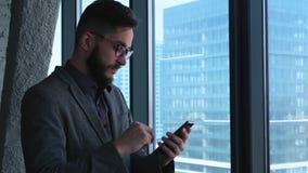 Успех в бизнесе и достижение - праздновать счастливого бизнесмена веселя на сотовом телефоне Молодой городской профессионал акции видеоматериалы
