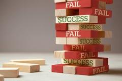 Успех и терпеть неудачу Деревянная башня блоков Отказ как новый шаг для успеха Отказ дает опыт и делает вас успешный стоковые фото