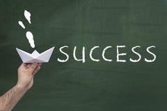 Успех, концепция достижения Человеческая рука держа бумажный корабль против зеленого классн классного с словом: УСПЕХ стоковые фото