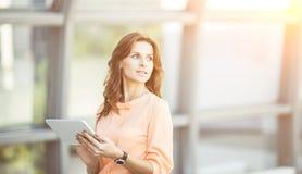 Успешная бизнес-леди при цифровая таблетка стоя около большого окна в современном офисе Стоковая Фотография RF