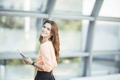 Успешная бизнес-леди при цифровая таблетка стоя около большого окна в современном офисе Стоковое Изображение RF