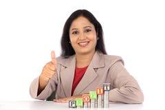 Успешная бизнес-леди с стогом монеток и делать большого пальца руки вверх Стоковые Изображения RF