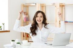 Успешная бизнес-леди при оружия вверх сидя в современном офисе стоковая фотография rf