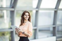 Успешная бизнес-леди при цифровая таблетка стоя около большого окна в современном офисе Стоковое Фото