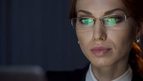 Успешная бизнес-леди смотря ноутбук, отражение экрана в eyeglasses стоковые фото