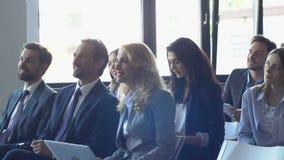 Успешная группа в составе бизнесмены слушая к представлению на тренировочном семинаре, команда Siiting предпринимателей на строке видеоматериал
