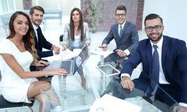 Успешная команда дела сидя на Des офиса стоковое фото rf
