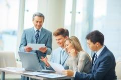 Успешная команда дела обсуждая план компании в офисе Стоковые Изображения RF