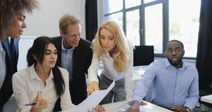 Успешная команда обсуждая бизнес-план на встрече в современном творческом офисе, группе предпринимателей связывает делить видеоматериал