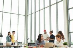 Успешная многонациональная команда дела в положении образа жизни по заведенному порядку работы творческом, сидя и говоря совместн стоковое фото