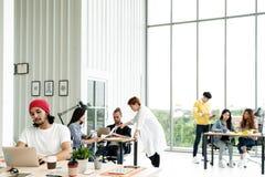 Успешная многонациональная команда дела в положении образа жизни по заведенному порядку работы творческом, сидя и говоря совместн стоковое изображение