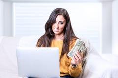 Успешная молодая бизнес-леди держа долларовые банкноты денег в руке стоковое фото rf