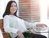 Успешная молодая бизнес-леди сидя на рабочем месте стоковые изображения