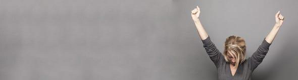Успешная молодая женщина выигрывая с обоими оружиями вверх, космос экземпляра стоковое изображение rf
