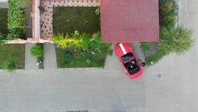 Успешная пара в красной спортивной машине cabriolet паркует рядом дом в деревне коттеджа элиты и приходит домой r акции видеоматериалы