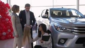 Успешное приобретение автомобиля семьи, дружелюбный женский продавец автомобиля кладет ключи в руки маленькой девочки с родителям сток-видео