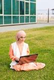Успешные арабские женщина и компьтер-книжка Hijab арабской коммерсантки нося работая на компьтер-книжке в парке Стоковые Изображения