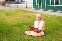 Успешные арабские женщина и компьтер-книжка Hijab арабской коммерсантки нося работая на компьтер-книжке в парке Стоковое фото RF