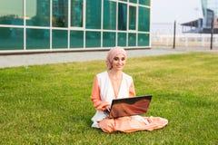 Успешные арабские женщина и компьтер-книжка Hijab арабской коммерсантки нося работая на компьтер-книжке в парке Стоковые Фото