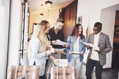 Успешные бизнесмены используют устройства, говорят и усмехаются во время перерыва на чашку кофе в офисе Стоковая Фотография