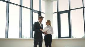 Успешные бизнесмены обсуждая бизнес-план около окна акции видеоматериалы
