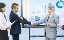 Успешные бизнесмены тряся руки приветствуя один другого на графиках предпосылки Стоковое фото RF