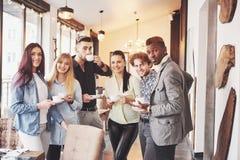 Успешные молодые бизнесмены говорящ и усмехающся во время перерыва на чашку кофе в офисе Стоковая Фотография RF