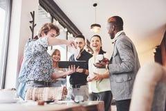Успешные молодые бизнесмены говорящ и усмехающся во время перерыва на чашку кофе в офисе Стоковая Фотография