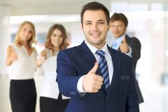 Успешные молодые бизнесмены показывая большие пальцы руки поднимают знак стоковые изображения