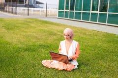 Успешные мусульманские женщина и компьтер-книжка Hijab арабской коммерсантки нося работая на компьтер-книжке в парке Стоковые Изображения
