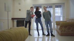 Успешный агент недвижимости показывает молодой женатой паре новый дом Счастливый человек и женщина смотря вокруг арендованный или видеоматериал
