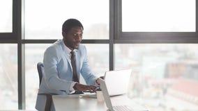 Успешный африканский бородатый предприниматель в небесно-голубом пальто ища полезное сведение видеоматериал