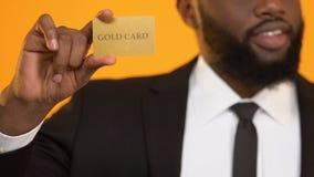 Успешный Афро-американский олигарх держа золотую жизнь богатых человеков кредитной карточки акции видеоматериалы