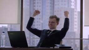 Успешный бизнесмен в офисе поднимает его руки вверх в знаке победы видеоматериал