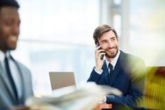 Успешный бизнесмен говоря на телефоне в офисе Стоковое Изображение