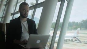 Успешный бизнесмен использует компьтер-книжку пока ждущ полет на авиапорте акции видеоматериалы