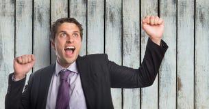 Успешный бизнесмен кричащий пока обхватывая кулаки против деревянной стены Стоковое Изображение