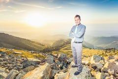 Успешный бизнесмен наверху горы смотря камеру Стоковые Фотографии RF