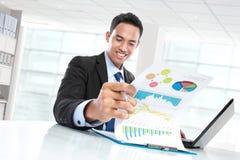 Успешный бизнесмен показывая диаграмму и усмехаться роста стоковые изображения