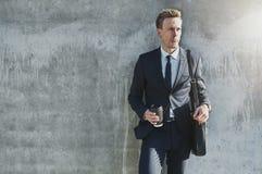 Успешный бизнесмен представляя с чашкой кофе Стоковое фото RF