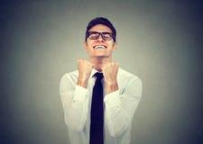 Успешный бизнесмен при нагнетенные кулаки празднующ успех стоковое изображение
