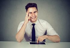Успешный бизнесмен при таблетка сидя на столе усмехаясь смотрящ камеру стоковое фото rf